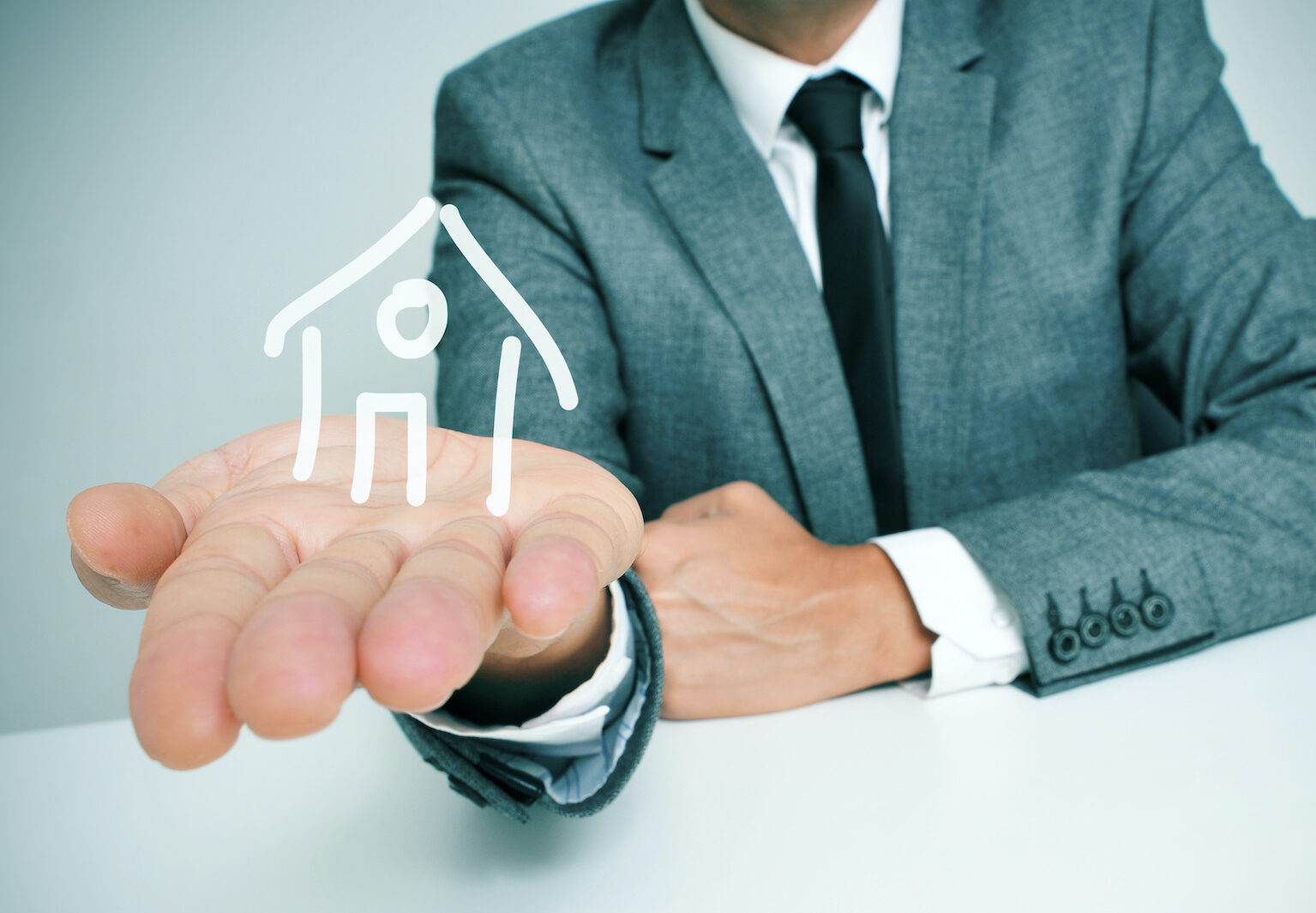 Public adjuster or private adjuster holding a symbol of a house in hand
